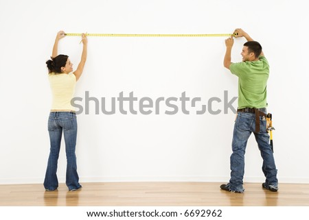 Couple measuring interior wall and smiling. - stock photo
