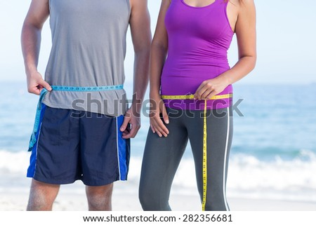 Couple measuring their waist at the beach - stock photo