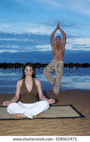 Couple meditating late afternoon at a beach