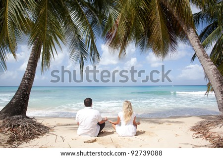 couple meditating on the beach under palm trees