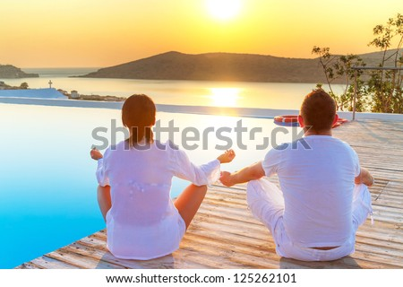 Couple meditating together at sunrise - stock photo