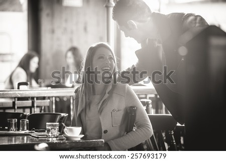 Couple meeting at the bar smiling at each other - stock photo