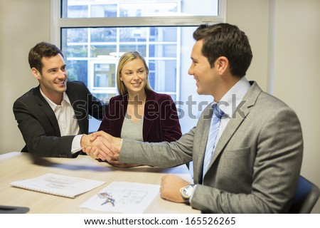 Couple meeting with financial adviser, handshake - stock photo