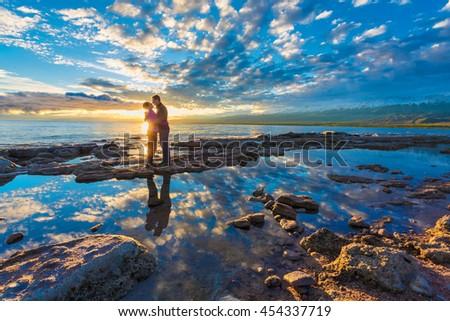 couple meets sunrise on the beach - stock photo