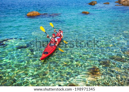 Couple men floating on a sea kayaking. Traveling by kayak outdoors on a summer day. - stock photo