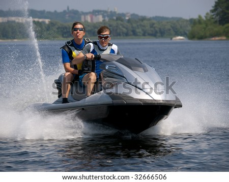 Couple men on jet ski in the river and one of man shows his tongue - stock photo