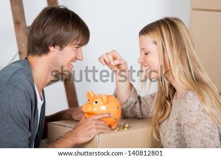 couple moving and thowing coins in a piggybank - stock photo