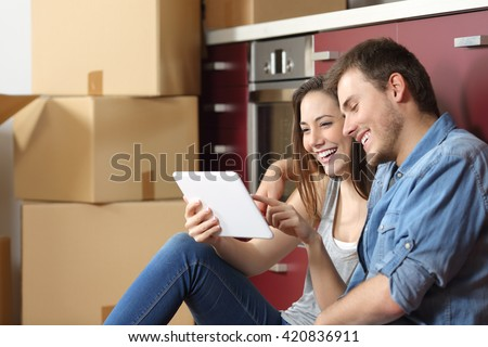 Couple moving home and buying on line with a tablet sitting on the floor in the kitchen - stock photo