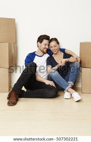 Couple moving home and sitting with boxes, smiling
