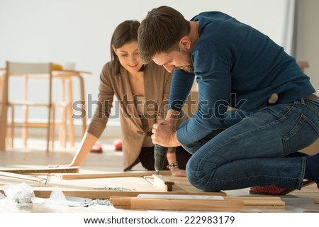 Couple moving in new home house. Unpacking boxes and assembling furniture - stock photo