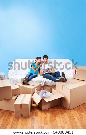 couple moving in together relaxing on sofa couch with laptop tablet computer and boxes - stock photo