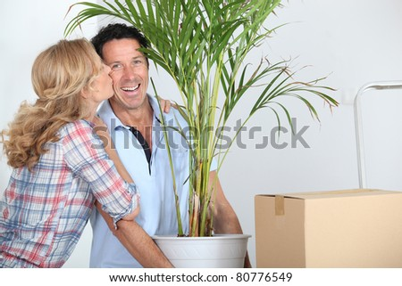 Couple moving in with plant - stock photo