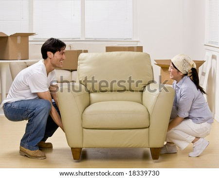 Couple moving into new home and placing armchair in livingroom - stock photo