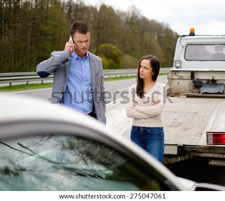 Couple near broken car on a roadside  - stock photo