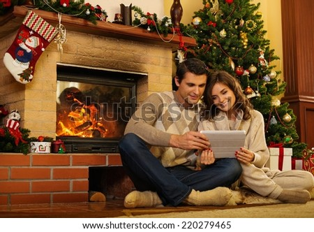 Couple near fireplace in Christmas decorated house with tablet pc