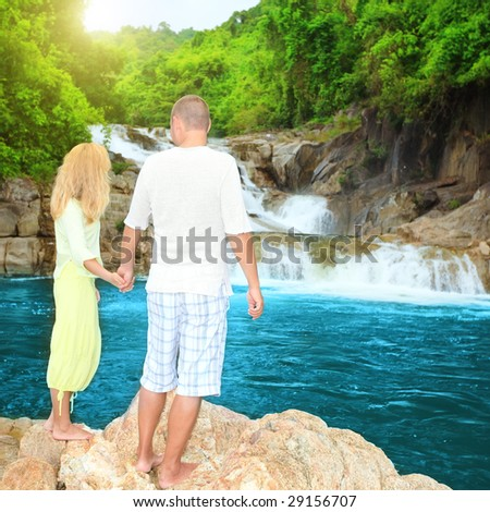 Couple near waterfall at sunrise time