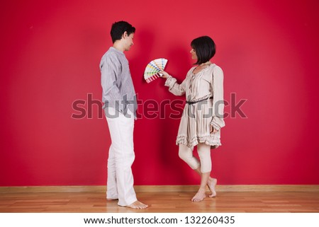 couple next to a red wall looking to a color paint palette (selective focus) - stock photo
