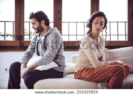 Couple not talking after a fight on the sofa in living room at home - stock photo