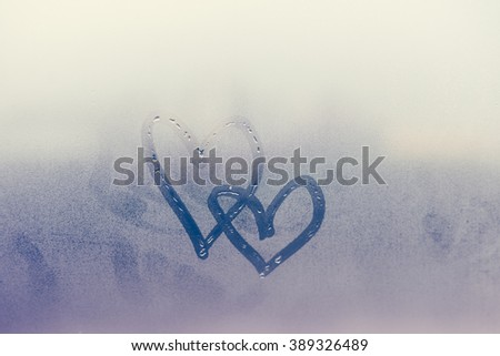 Couple of abstract blurred love heart symbol drawn by hand on the wet frozen window glass with sunlight background. Selective focus used. - stock photo