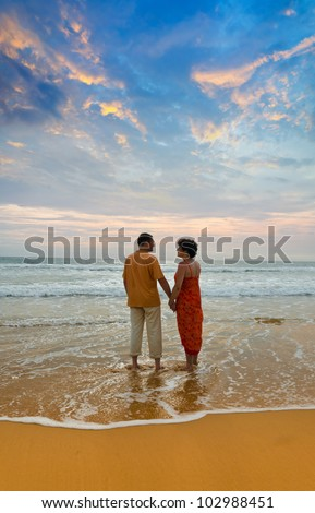 couple of adults on ocean shore at sunset - stock photo