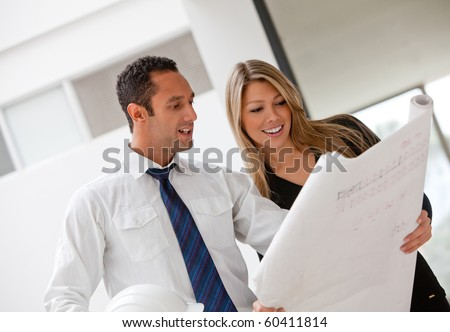 Couple of architects at the office looking at blueprints - stock photo