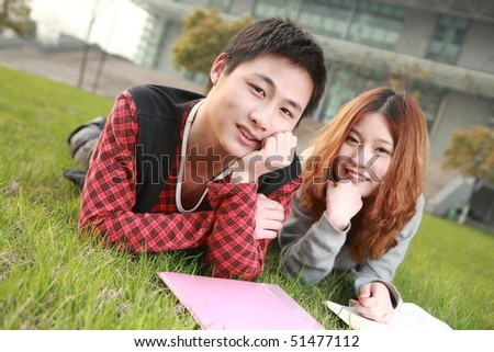 couple of asian  reading book on grass