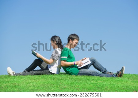Couple of Asian students outdoors looking very happy - stock photo