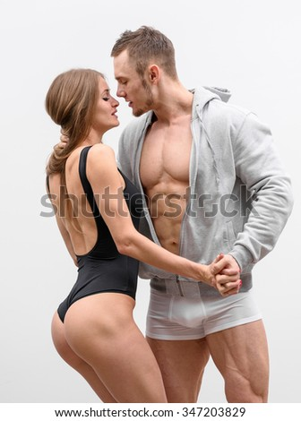 Couple of athlete lovers posing on grey background.
