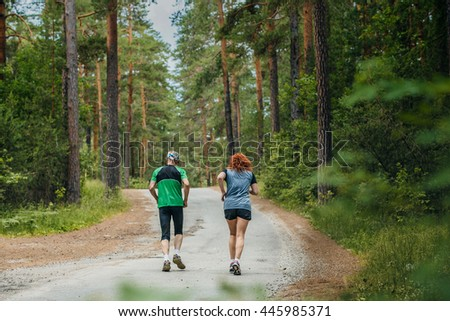 couple of athletes, a man and woman running along road in forest during a marathon