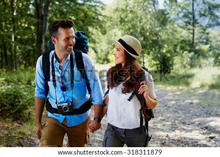 Couple of backpackers hiking together - stock photo