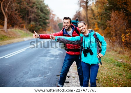 Couple of backpackers hitching. Stopping car on the road - stock photo