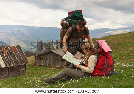 Couple of backpackers on top of mountain with map  - stock photo