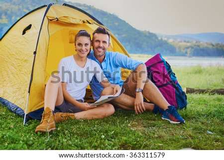 Couple of backpackers sitting outside the tent - stock photo