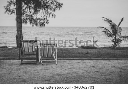 Couple of beach chairs on sea coast at thailand - black and white - stock photo