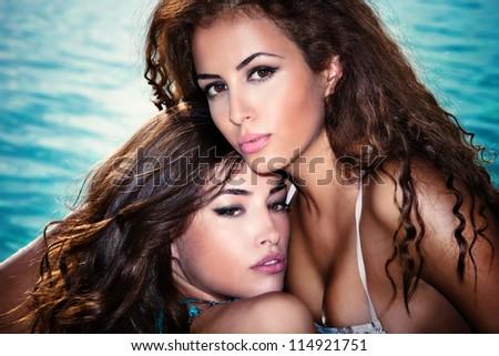 couple of beautiful girls portrait by the swimmingpool - stock photo