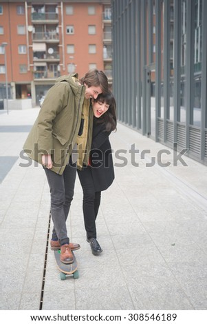 Couple of beautiful woman and man, with moustache and skate,walking through the streets of the city hugging, playing and chatting- freshness, youth, carefreeness concept