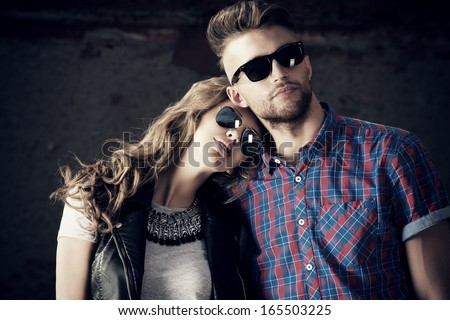 Couple of beautiful young people in love posing outdoors over brick wall. - stock photo