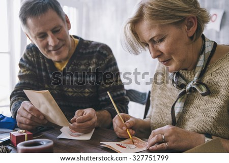 Couple of blonde woman and brunet man painting Christmas cards using brush - stock photo