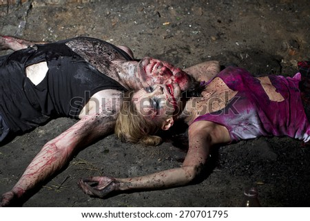 Couple of bloody man and woman lying on the ground - stock photo