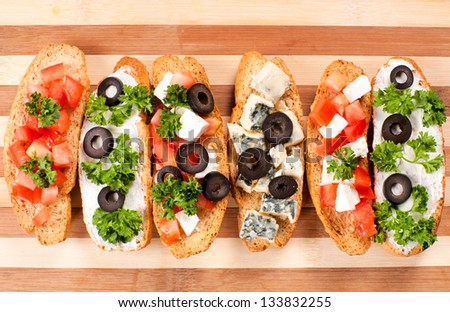 Couple of Bruschettas on the wooden board - stock photo
