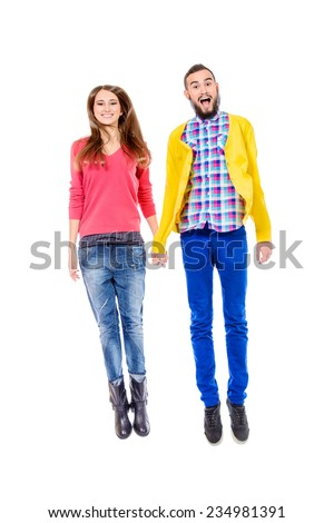 Couple of cheerful young people jumping for joy. Isolated over white. - stock photo