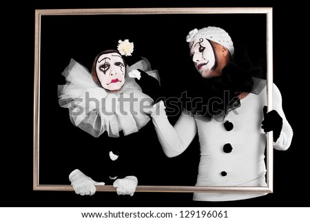 couple of clowns in a frame, one looks sorrowful - stock photo