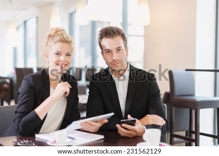 Couple of colleague  wearing suits, sitting at a table and using a digital tablet in a meeting - stock photo