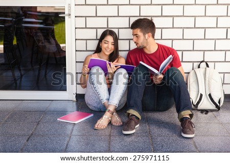 Couple of college students sitting outside a classroom and studying together - stock photo
