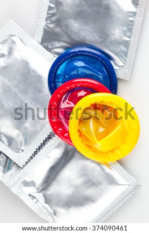 Couple of Colorful condoms with packaging, isolated on white background. - stock photo
