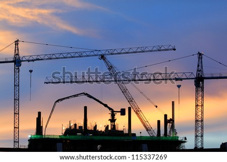 couple of cranes on a construction site with a blue evening sky backdrop - stock photo