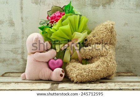 couple of cute bear dolls holding roses bouquet - stock photo
