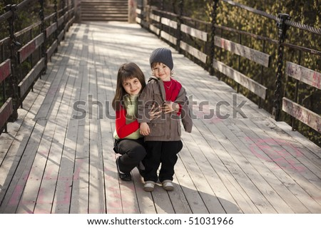 Couple of cute boy and girl on a bridge - stock photo