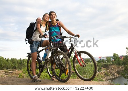 Couple of cyclers on their bikes embracing each other in the countryside - stock photo