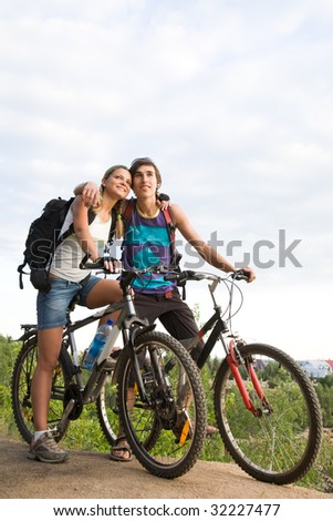 Couple of cyclers on their bikes embracing outdoors during trip - stock photo